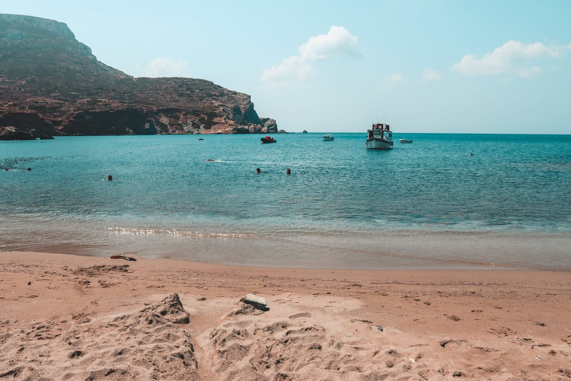 Agali beach with turquoise waters and a boat. Best beaches in Folegandros
