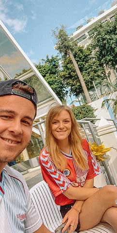 A couple taking a selfie at a hotel with trees in the background. Where to stay in Tenerife.
