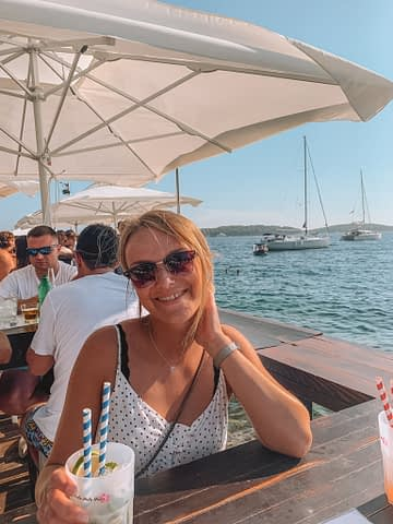 A woman having a cocktail in Hula Hula bar with the ocean in the background. Things to do in Hvar
