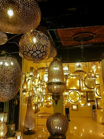 Golden ornaments hang from the ceiling in a Marrakech market.