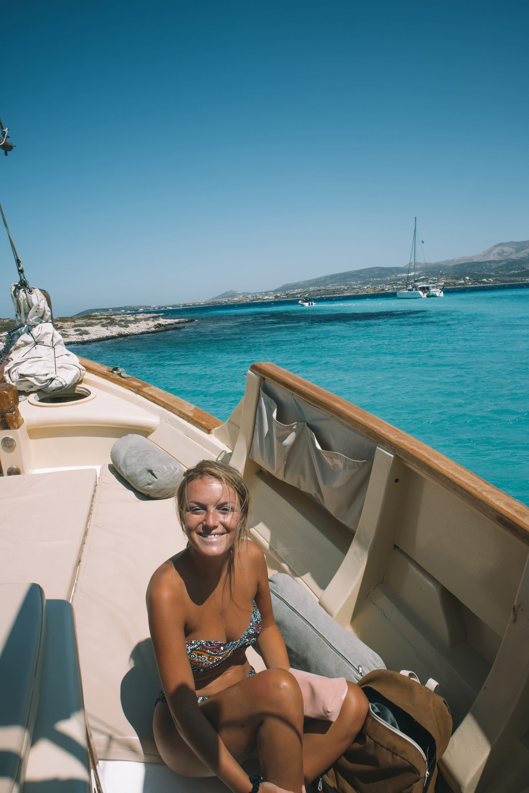 A woman smiling sat on a boat with the turquoise ocean in the background. Antiparos travel blog