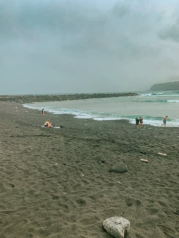 Black sandy beach with some people on it. Where to stay in Tenerife