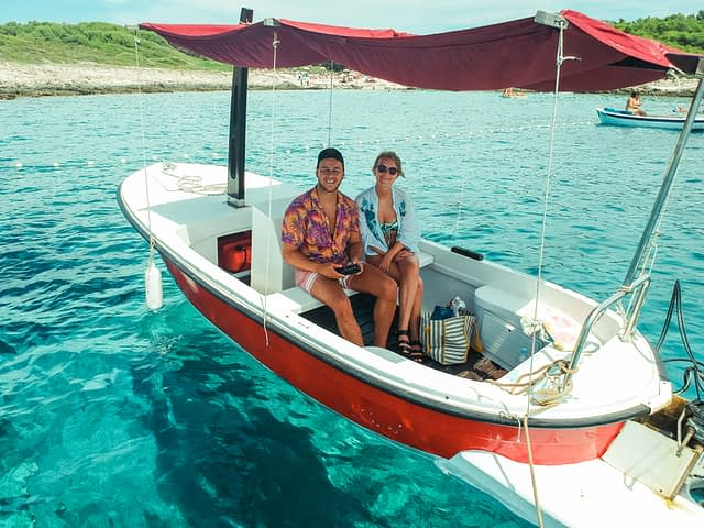 A couple sat in a rented boat, surrounded by turquoise water. Things to do in Hvar