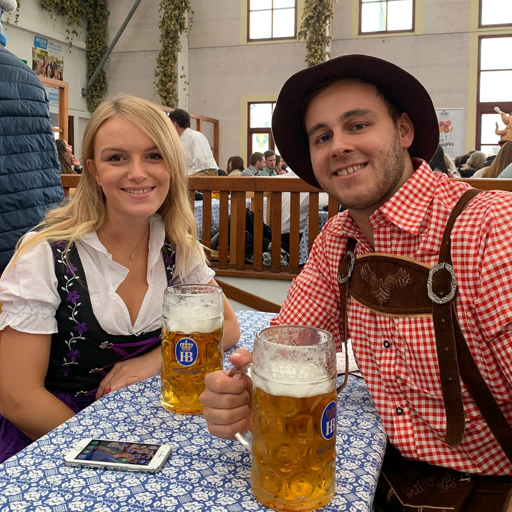 A couple in an Oktoberfest tent, part of what to do at Oktoberfest.