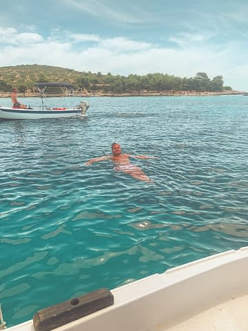 A man swimming in turquoise water near a boat. Things to do in Hvar
