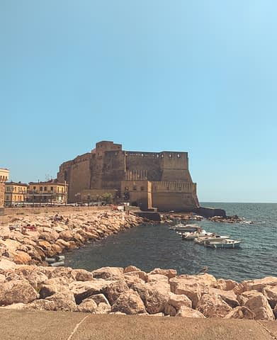 Ocean, boats and rocks with a castle in Naples. A day in Naples itinerary