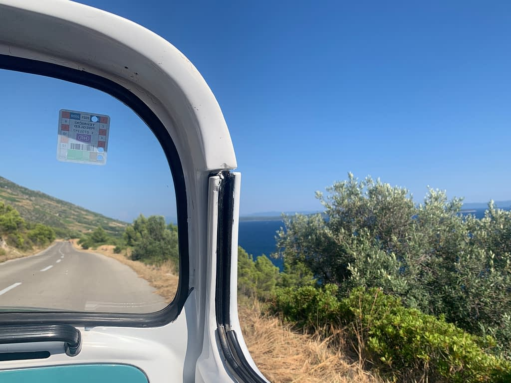 A convertible car with a view of the ocean, as part of the things to do in Hvar.