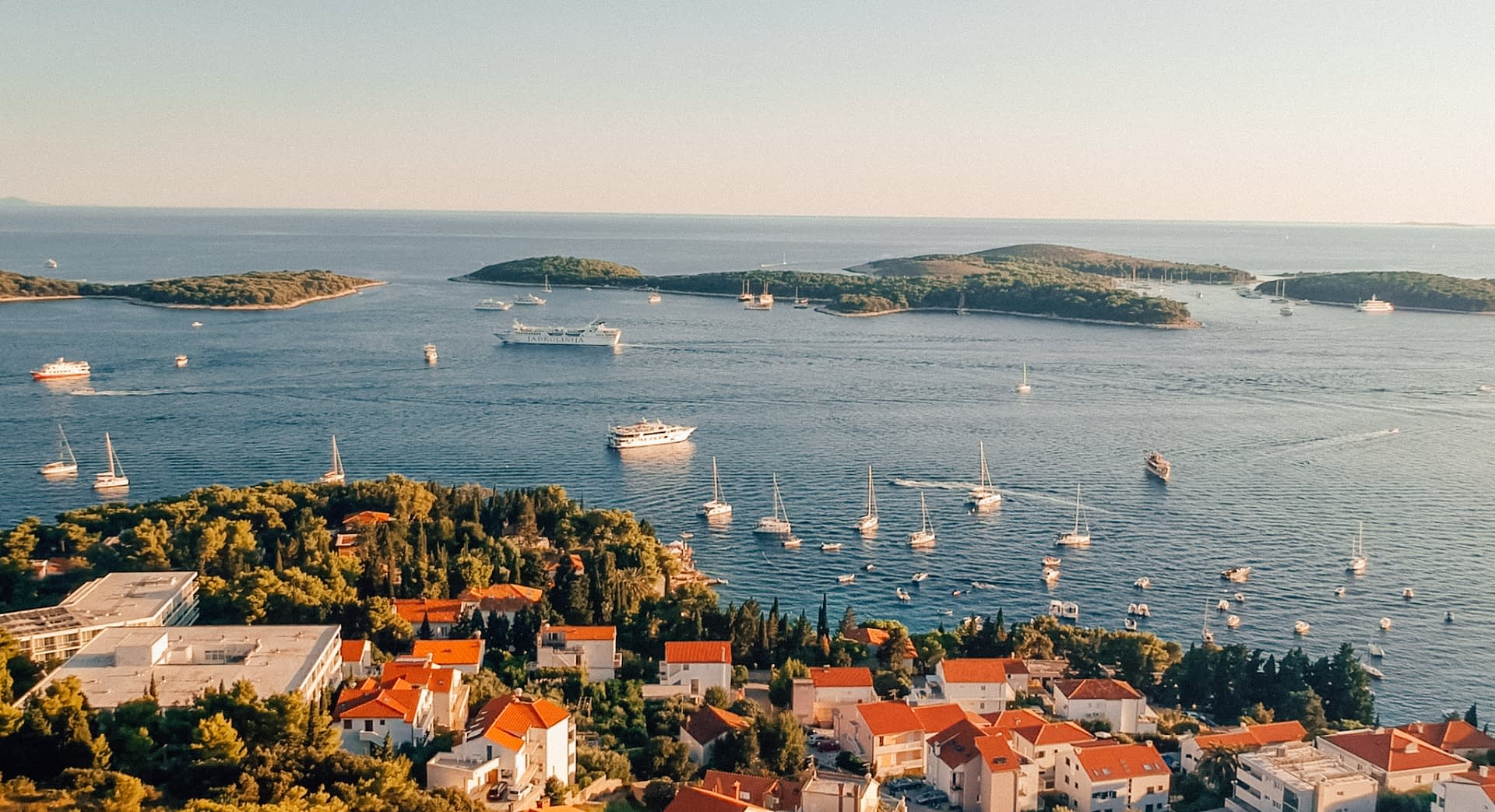 Hvar during sunset with islands and boats in the ocean. Things to do in Hvar