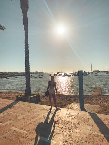 A woman in front of a palm tree with the sun shining.