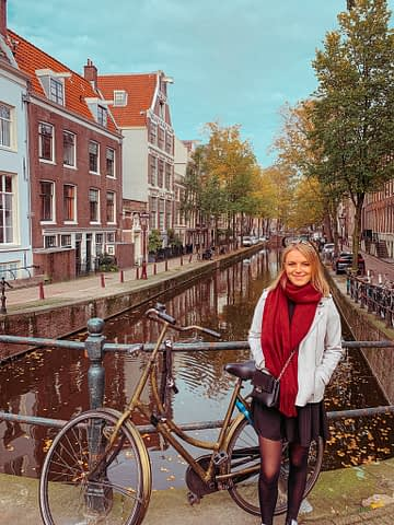 A woman stood on a bridge next to a canal with a bike as part of visiting Amsterdam on a budget.