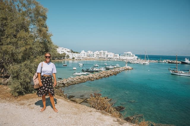 A woman stood on a hill with the Piso Livadi village harbour in the background. Paros travel blog