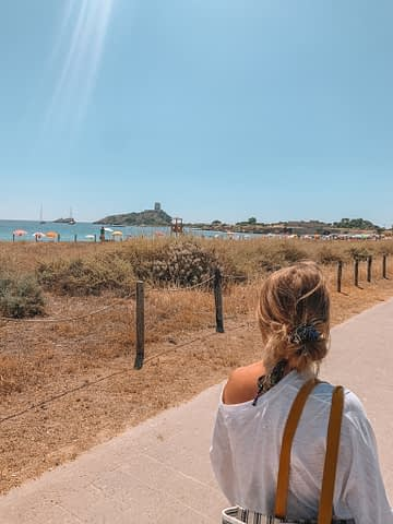 A woman walking up a path near the sea with a castle in the background. Things to do in Sardinia.
