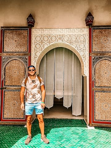 Le Jardin Secret. Man infront of entrance as part of the Morocco travel guide
