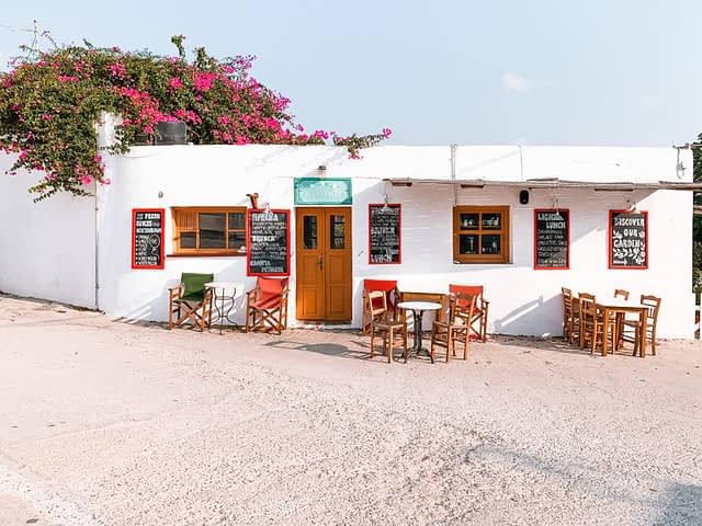A white Folegandros cafe with blossoming plants around it. Things to do in Folegandros