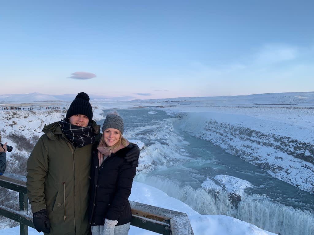 A couple stood in front of Gullfoss waterfall as part of the things to do in Iceland.
