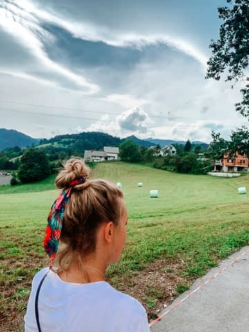 A woman walking near fields and farmland. Where to go in Bled