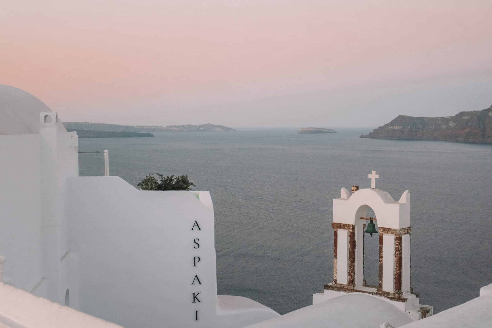 Whitewashed churches with the sunrise in the background.