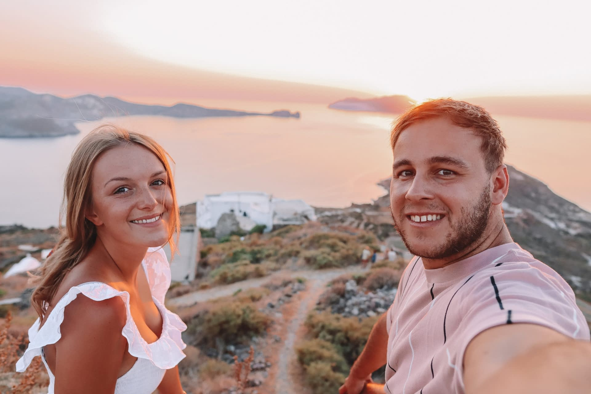 A couple taking a selfie with the ocean and islands in the background