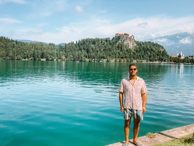 A man stood by the bank of the lake with a castle in the background in the hills. Things to do at Lake Bled