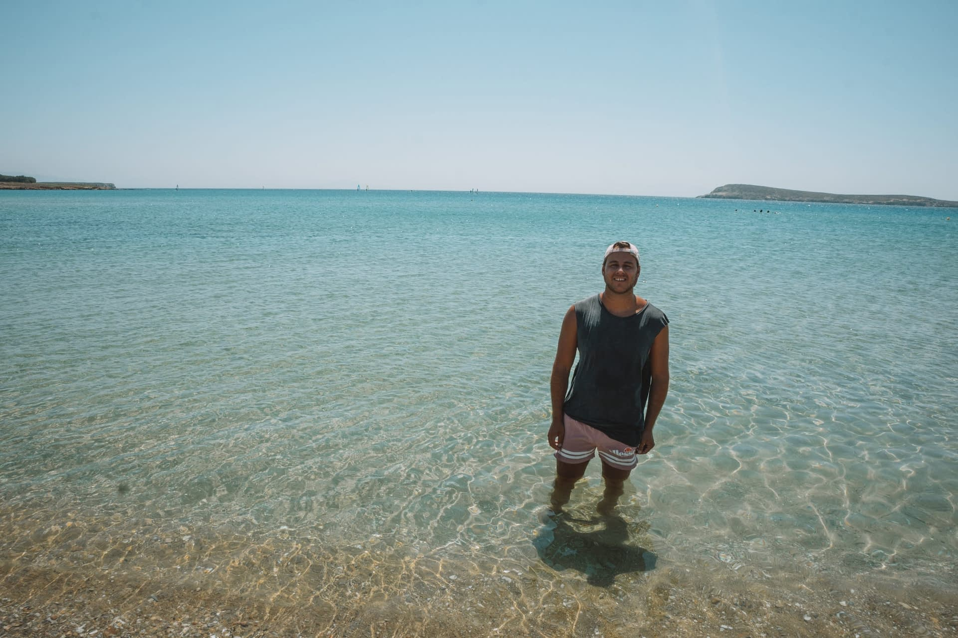 A man stood in turquoise water in Paros