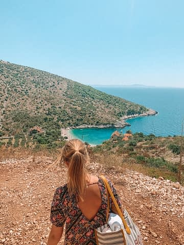 A view of Dubovika beach with turquoise water from the top of the mountain with a woman walking towards it. Best beaches in Hvar
