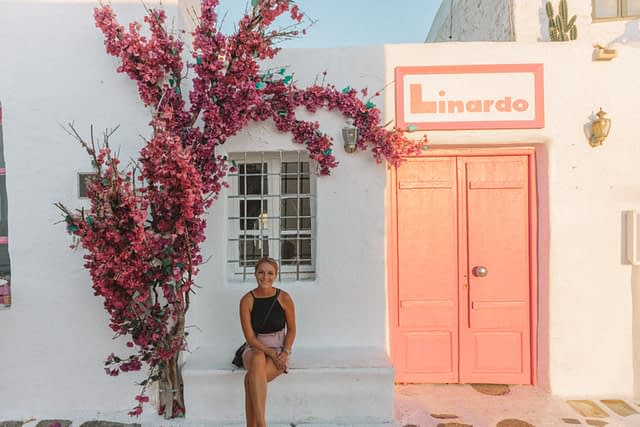 A woman sat on a white ledge next to pink flowers and a pink door in Naoussa.