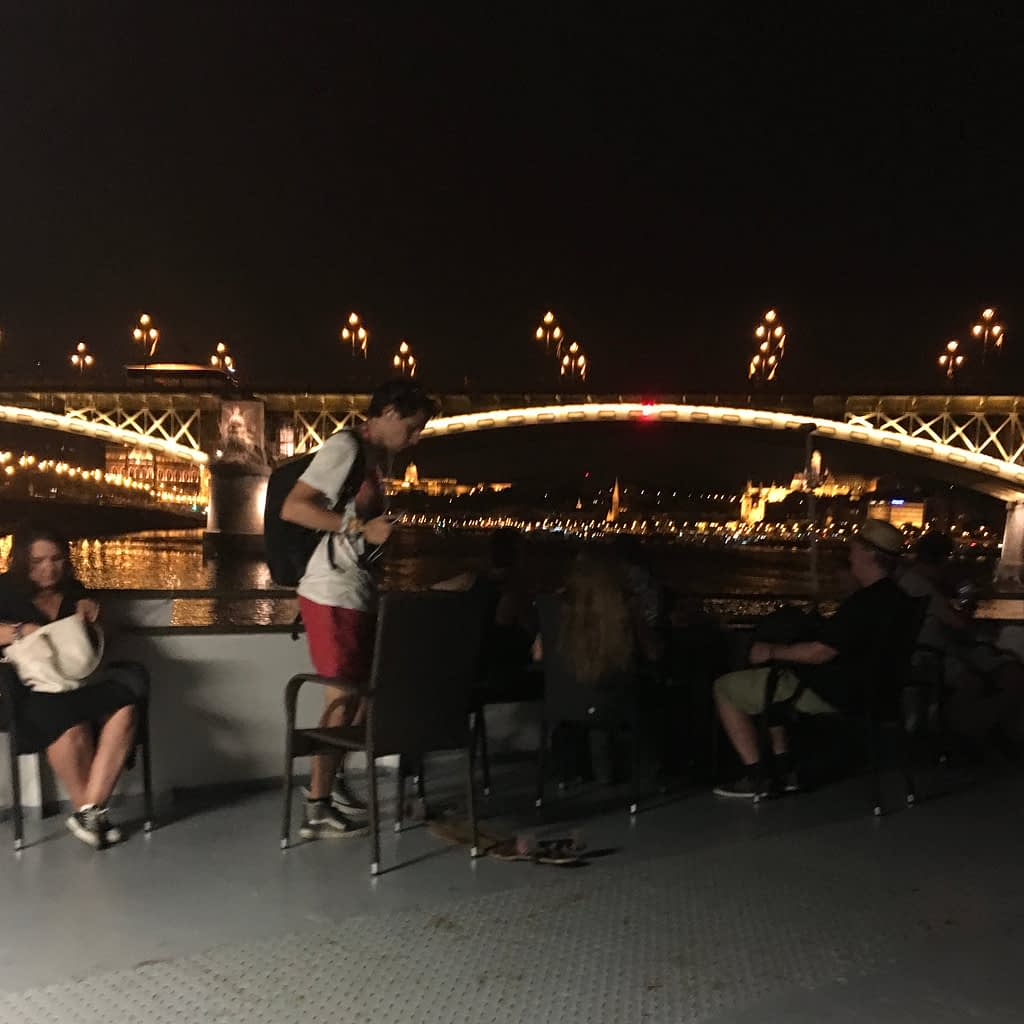 One of the many lit up Budapest bridges can be seen from a boat at night time.