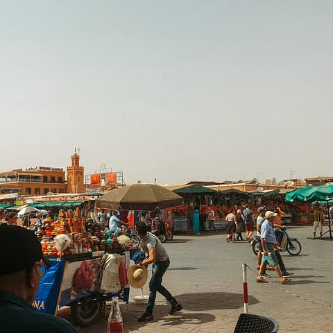 People and market stalls in an open Marrakech market. Part of the things to do in Morocco