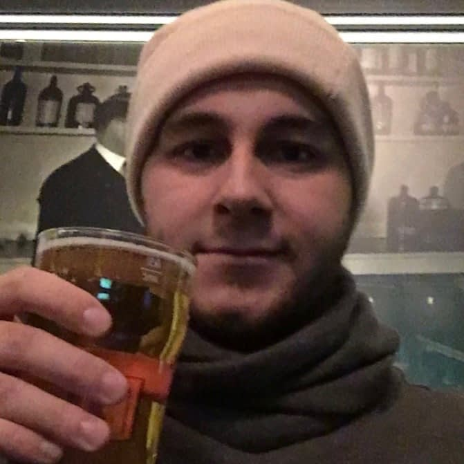 A man holding a pint of beer.