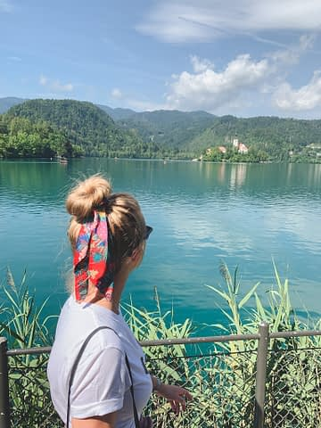 A woman looking across Lake Bled to Bled island with a church in the middle of it. What to do at Lake Bled