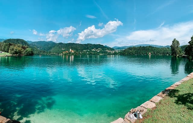 A wide angle view of Lake Bled and its surrounding areas with hills and an island in the background