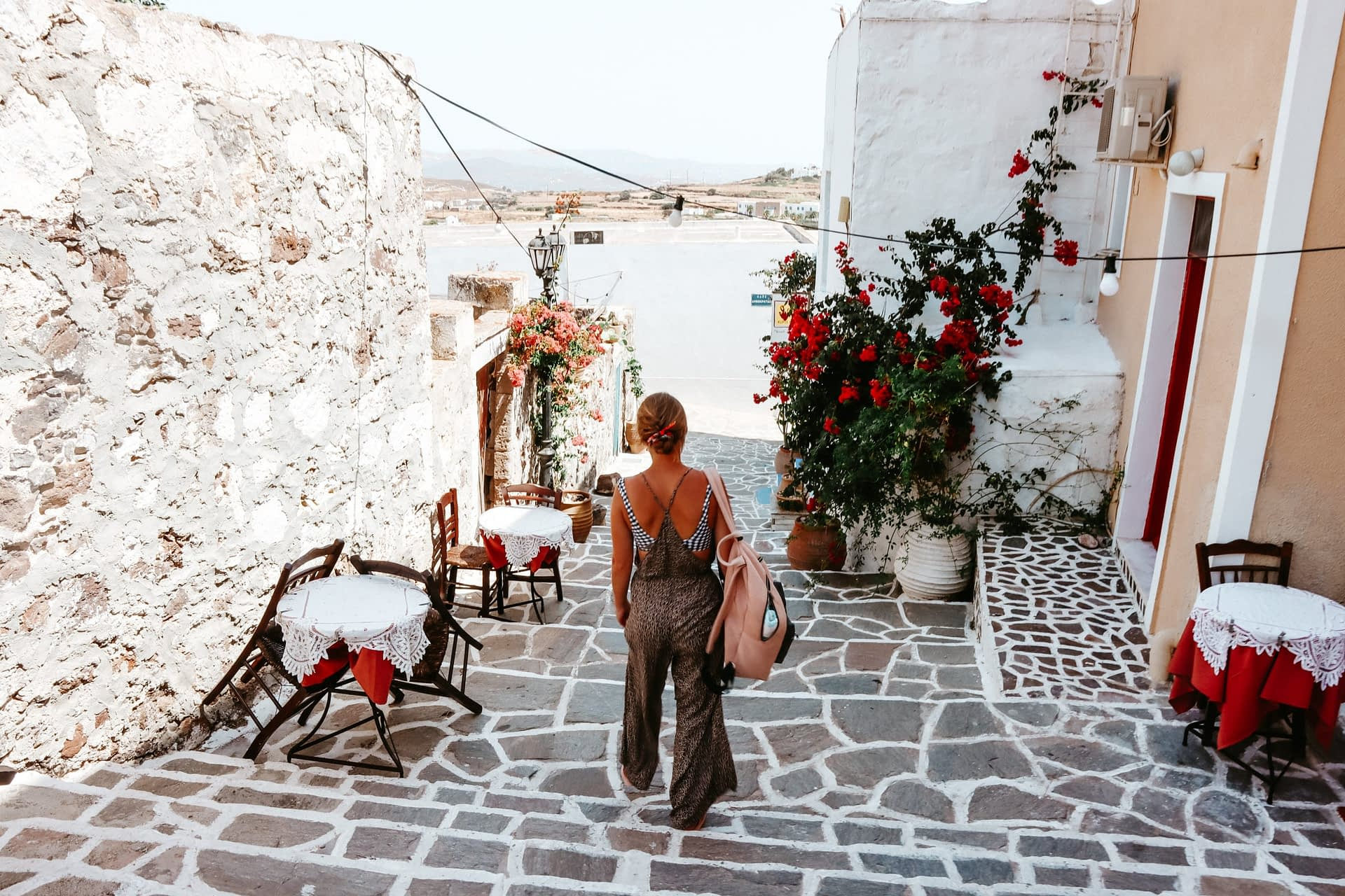 A woman walking down a narrow Greek street with flowers decorated around. Things to do in Milos