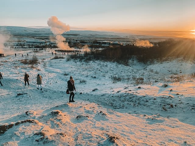 Stokkur Geysir with thick clouds of smoke coming from the snowy ground