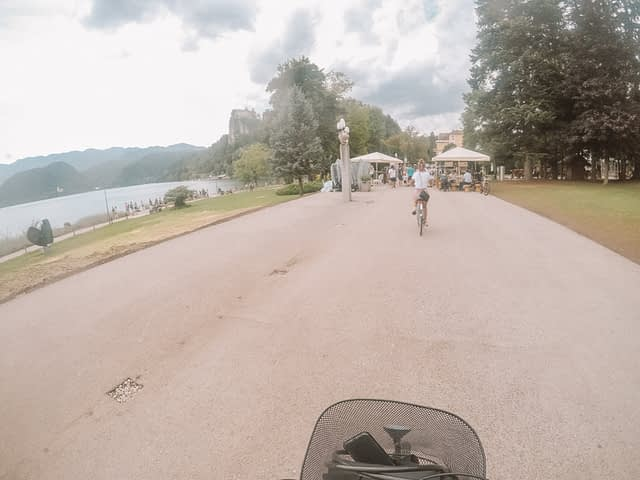 A woman in front of the camera riding a bike around Lake Bled. What to do at Lake Bled