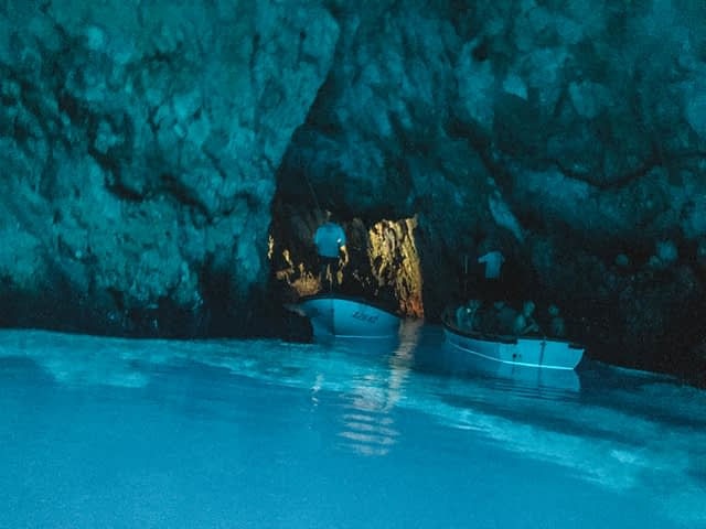 Blue sea water reflecting a blue light in a cave with boats in the water. Where to go in Hvar