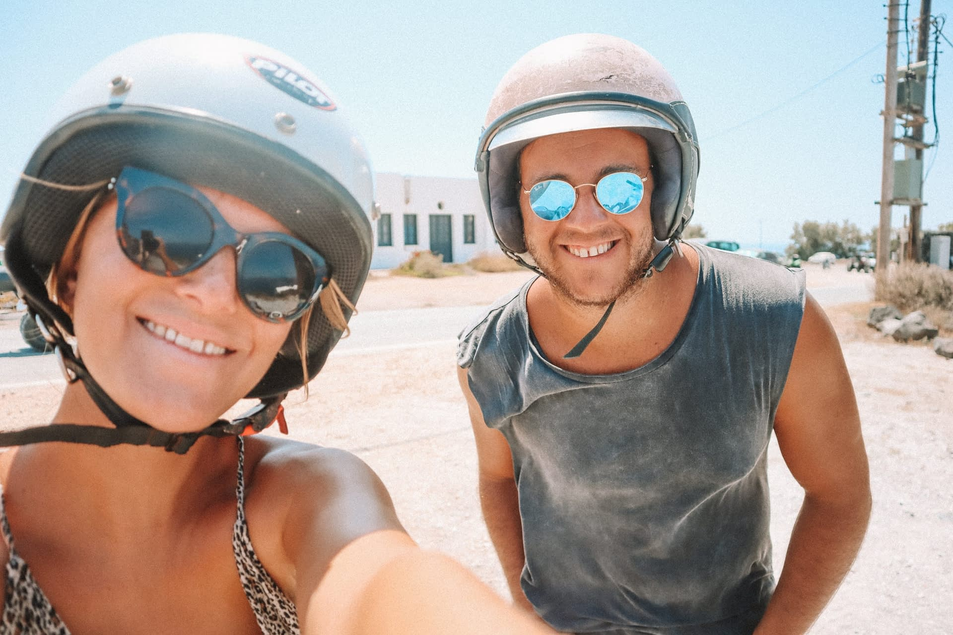A couple taking a selfie with helmets on. How to get around in Santorini