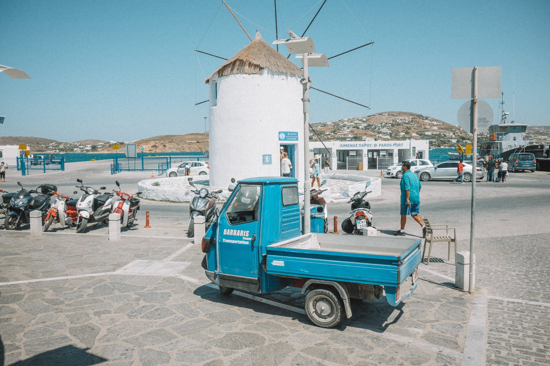 A three wheeled van in front of a windmill in Parakia, Paros. Things to do in Paros