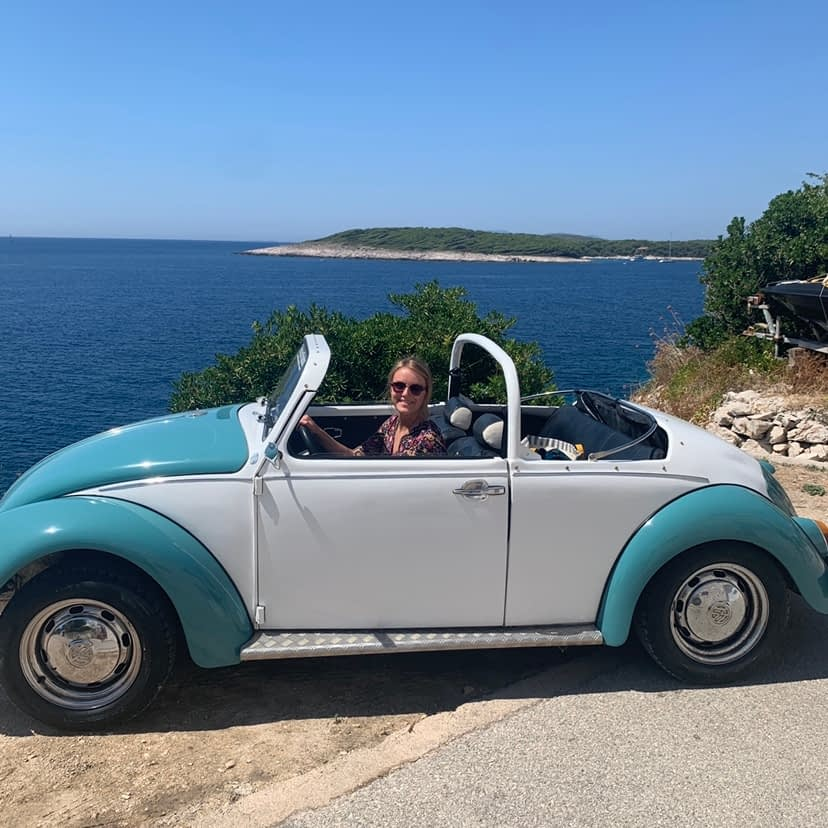 Blue and white Volkswagen convertible car with a woman as passenger