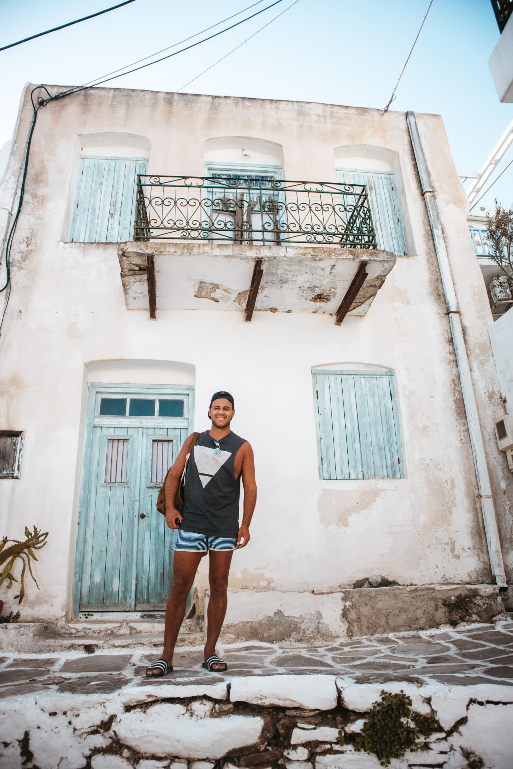 A man stood in front of a house in Lefkes village, Paros