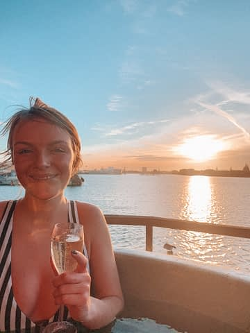 A woman with champagne with the sunset in the distance. 3 days in Copenhagen.