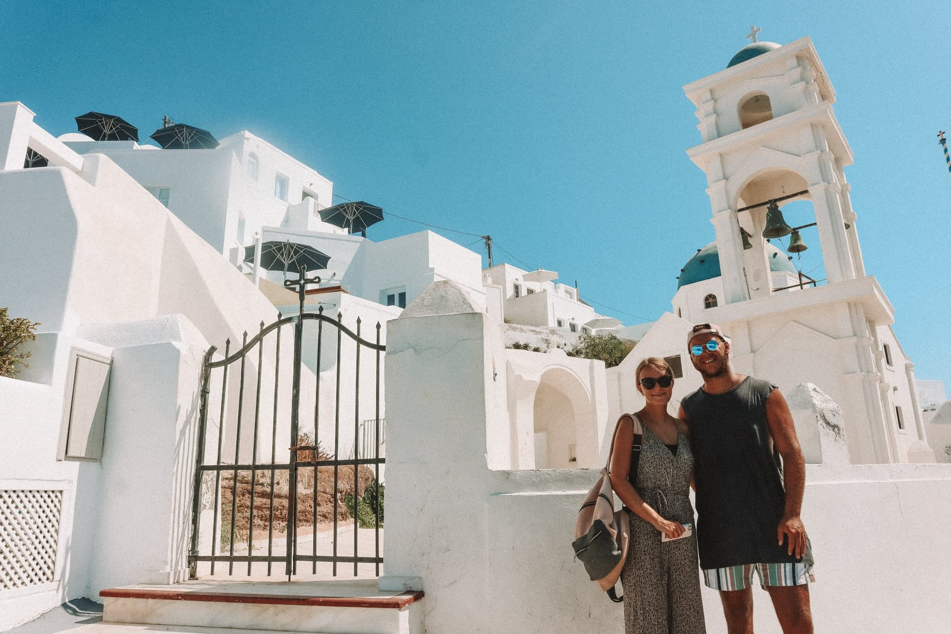 A couple in front of Imerovigli Greek church with bells