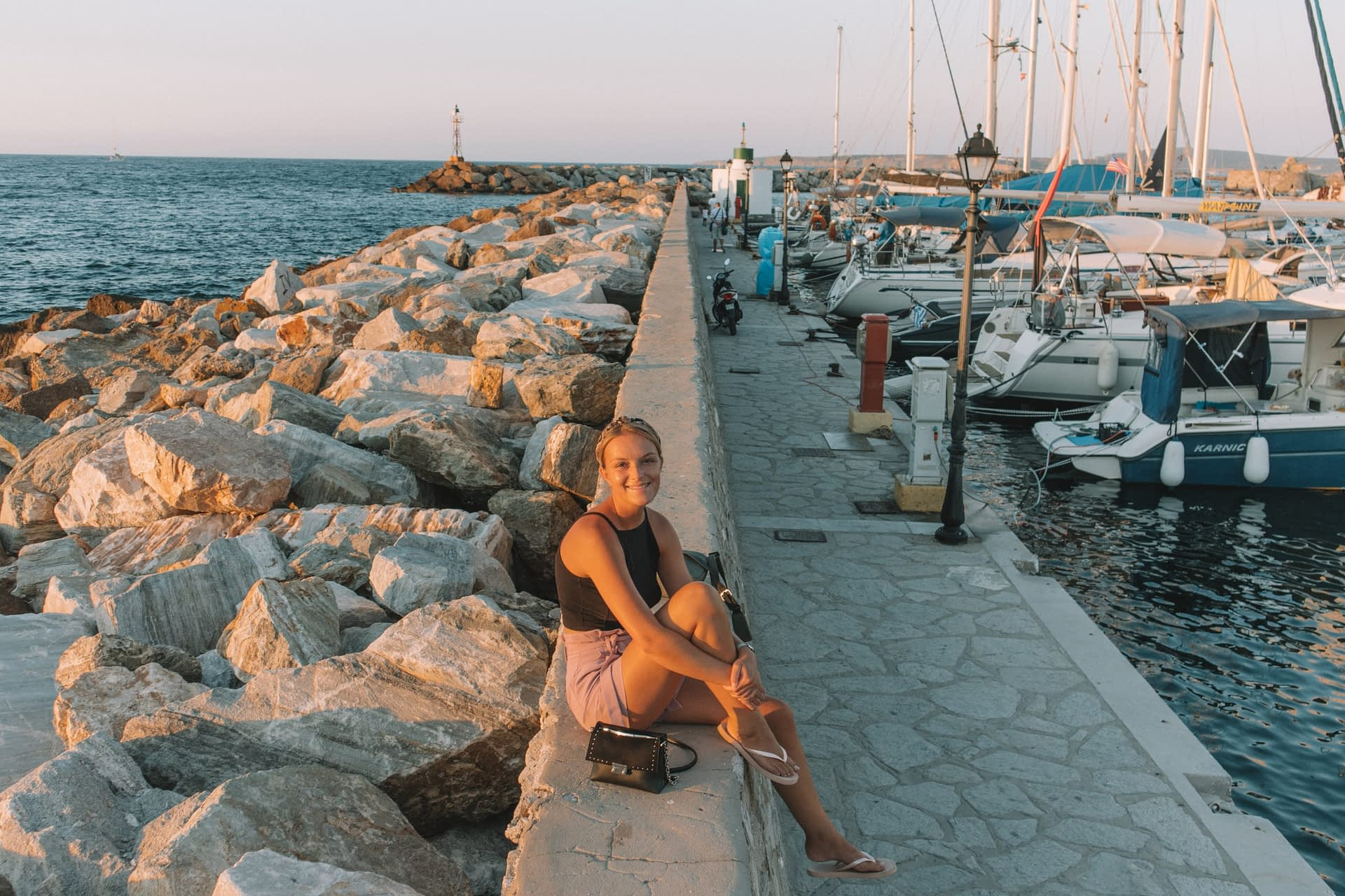 A woman next to the rocks and harbour of Naoussa during sunset.