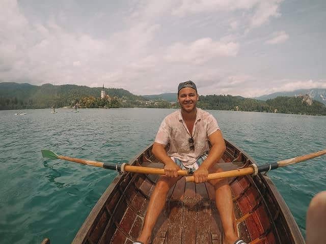 A man with some oars rowing in a boat at Lake Bled. What to do at Lake Bled