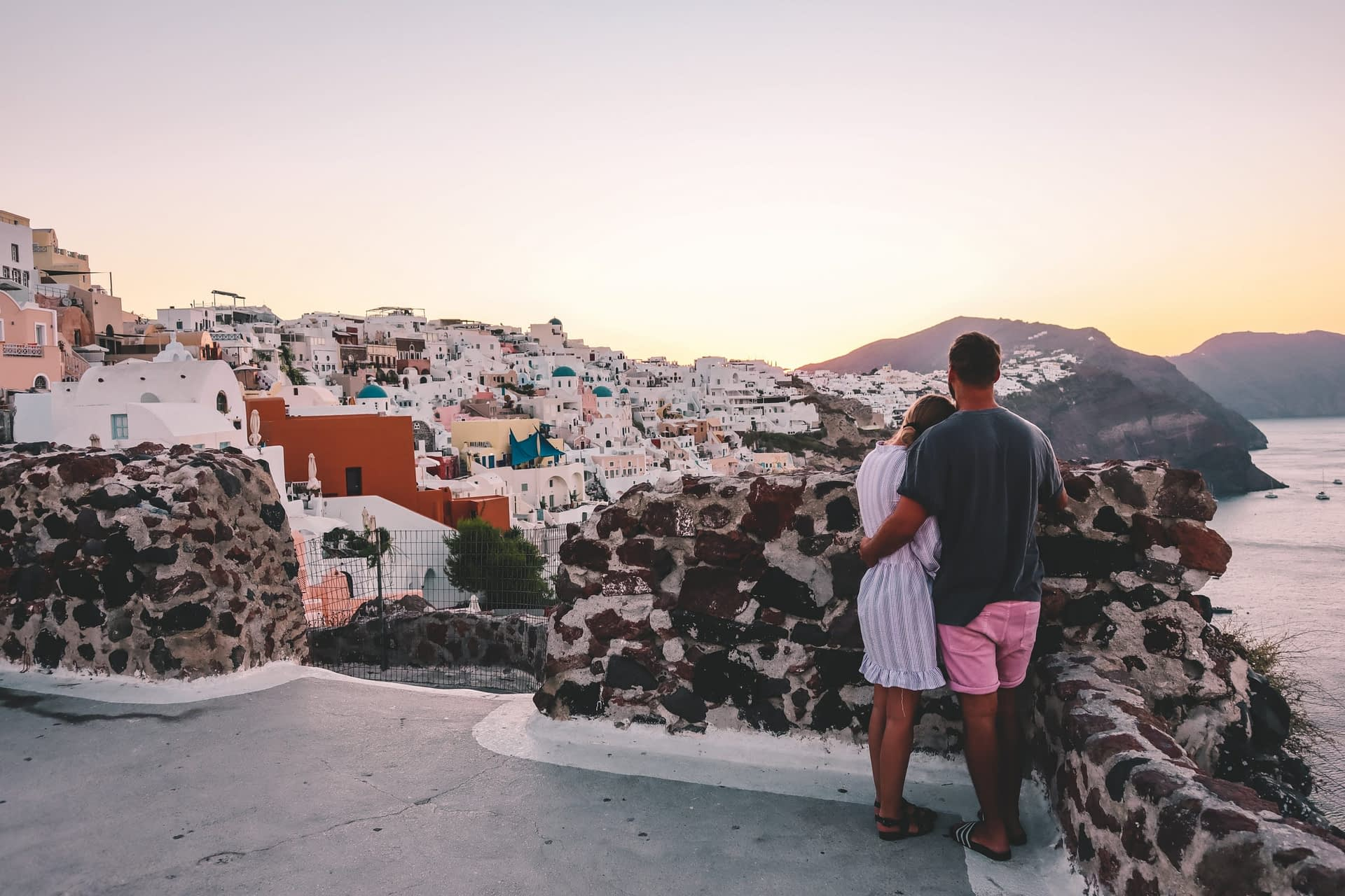 A couple stood watching the sunrise over Oia in Santorini.