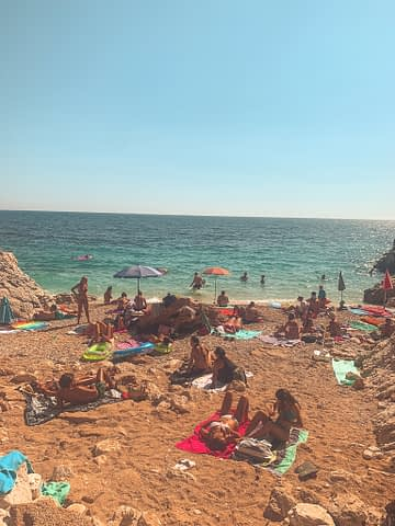 Jagodna Beach in Hvar with golden sand, lots of people and turquoise water
