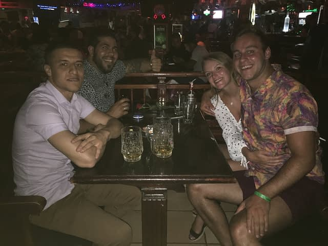 A group of people enjoying themselves with drinks in a bar