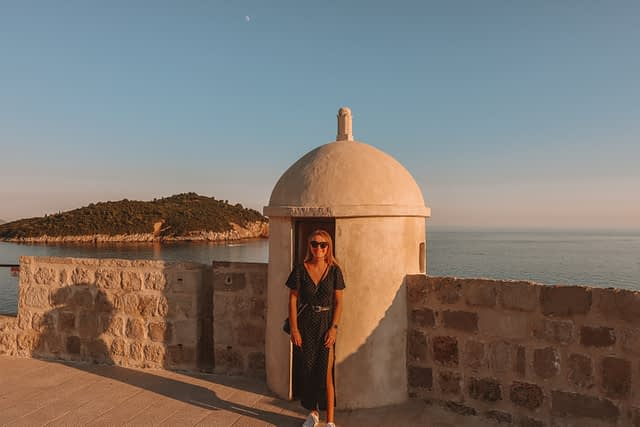 A woman stood in front of a turret on the Dubrovnik city walls with Lokrum in the distance