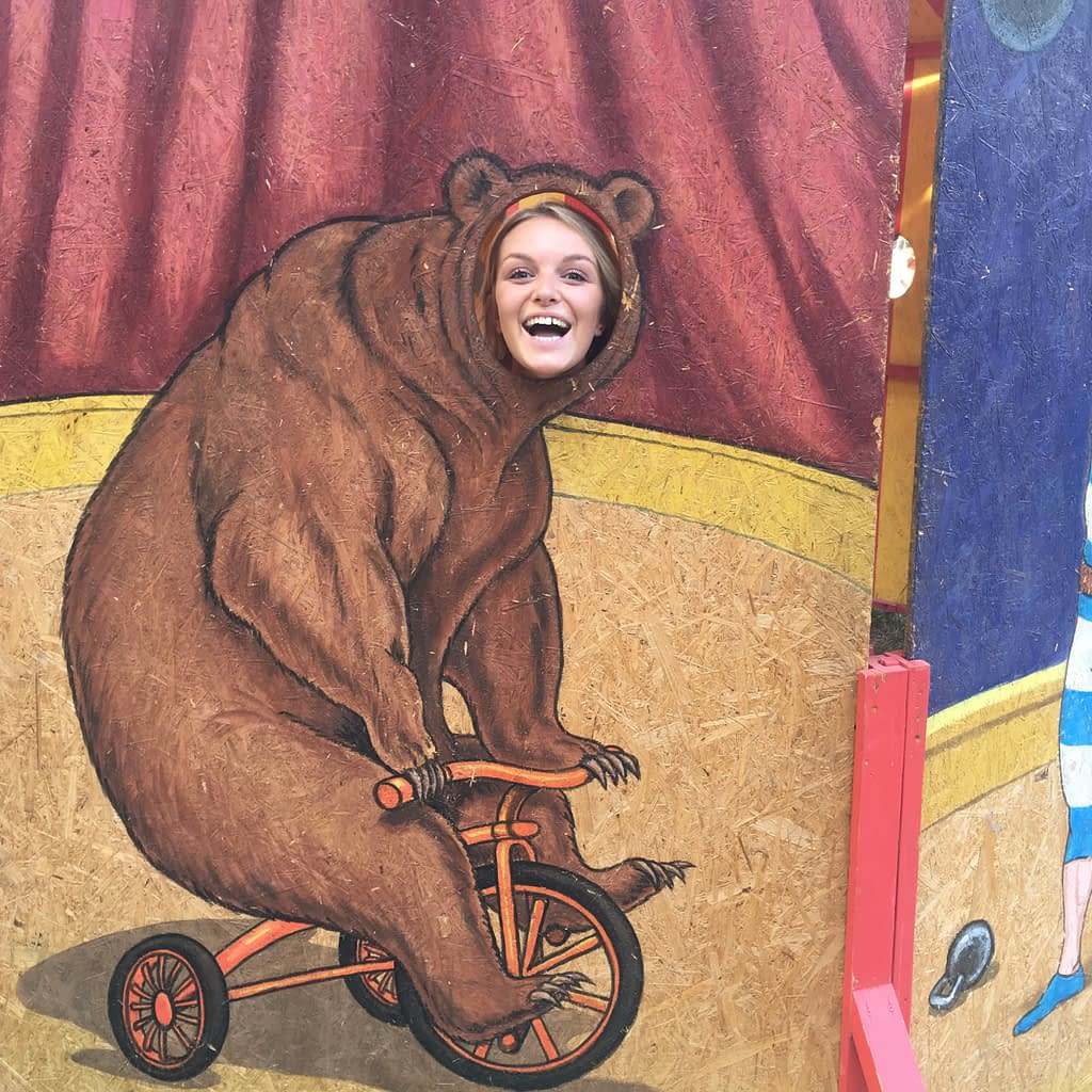 A woman with her head in a gap of a bear head. The circus is mentioned in the Sziget budapest guide.
