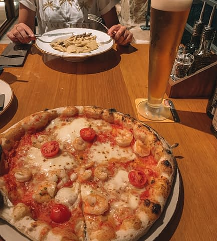 Pizza and pasta with a beer on a table at a restaurant in Hvar