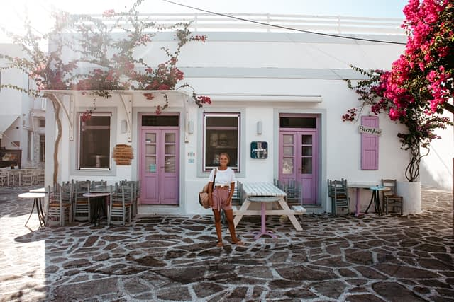 A woman stood in front of a pink and white colourful building in Antiparos.